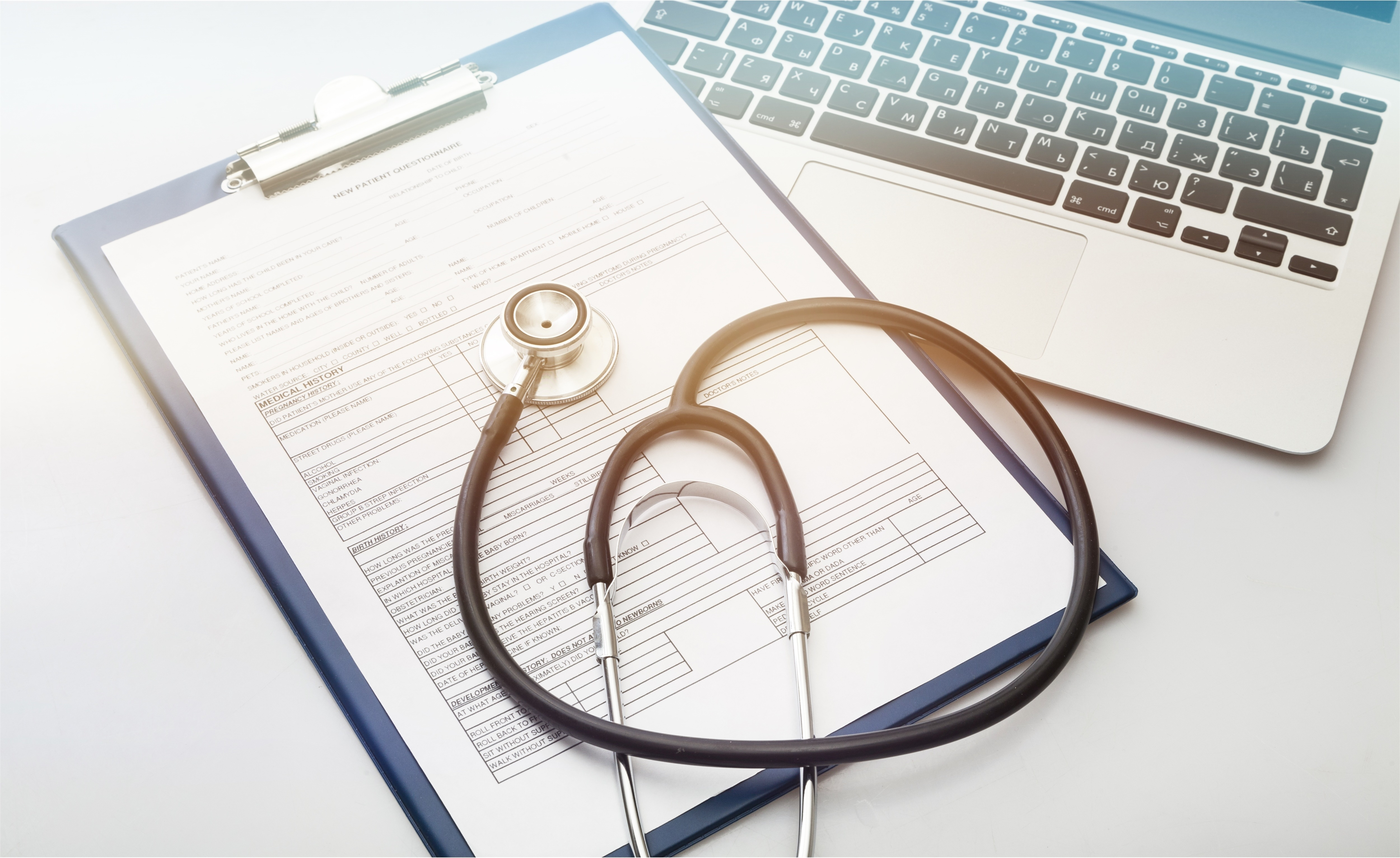 Modern laptop and stethoscope on wooden background